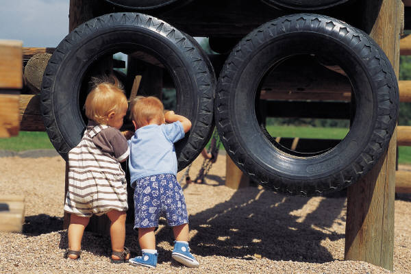 Two Toddlers looking into hanging tires