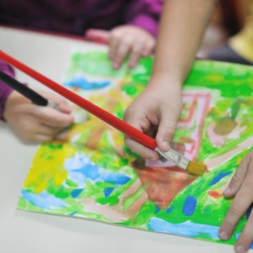 Two children working on a painting