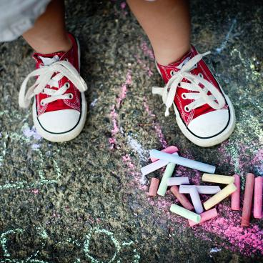 Child in red sneakers standing above chalk