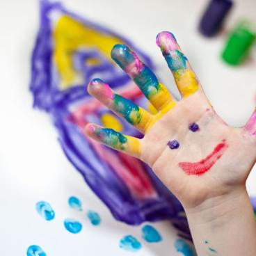 Child hand in finger paint with a smiley face in their palm