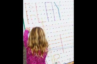 Child playing with strong on board with PLAY spelled out