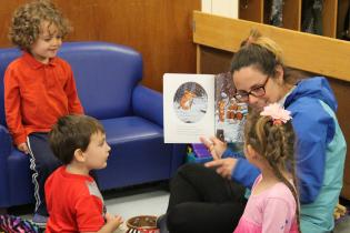 Student reading to three children in a circle