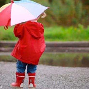Little girl holding an umbrella up