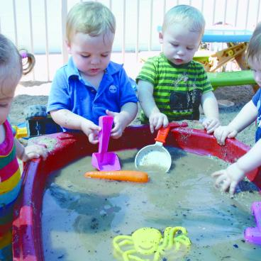 Toddlers playing in a water and sand tray