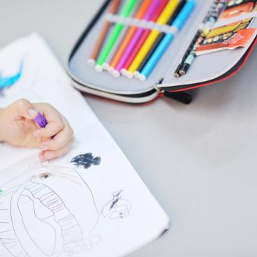 Child drawing in coloring book with markers