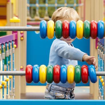 Child sliding circles across a bar at a park