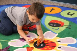 Toddler playing with a toy on a play mat