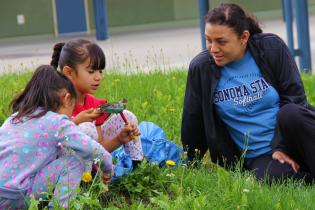 Student observing the natural world with two children