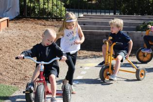 Kids playing on bikes and running.