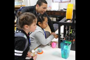 Teacher showing 3D printer to students
