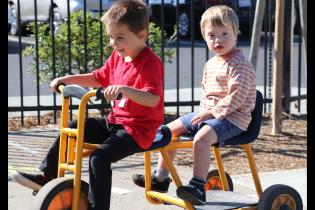 Two preschool children riding together on a bike